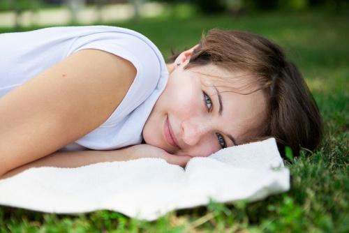 Mujer feliz y alegre acostada en prado